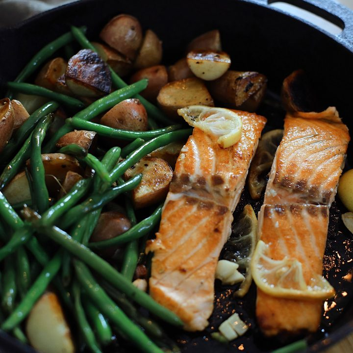 Wondering how to cook salmon? We've got such a simple and easy cast iron skillet salmon recipe with a delicious garlic lemon butter glaze. Pan seared salmon is an easy way to get it just right, every time… in fact, a kid can do it!