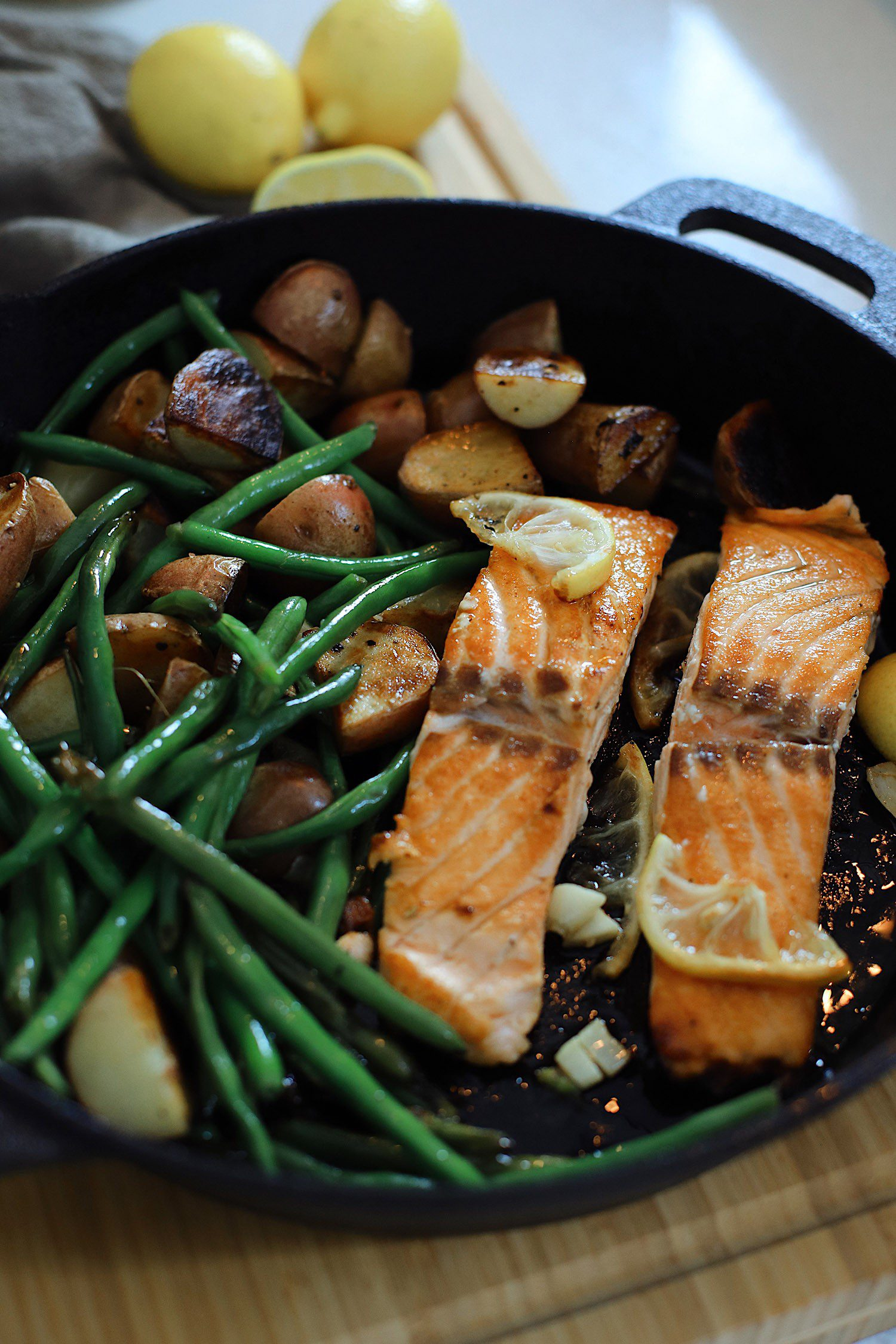 Wondering how to cook salmon? We've got such a simple and easy cast iron skillet salmon recipe with a delicious garlic lemon butter glaze. Pan seared salmon is an easy way to get it just right, every time. Perfect for a date night at home. Check out these valentines dinner ideas!