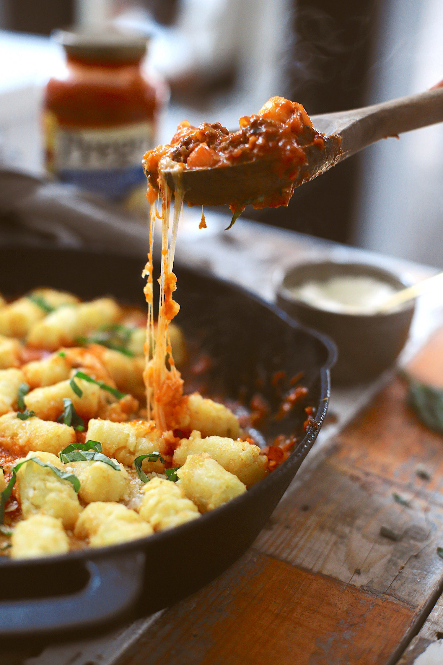 This simple one skillet Bolognese Tater Tot Casserole made with Prego® is a delicious family dinner that you can make perfect any time of year with pantry staples. Think of a cross between a classic bolognese pasta and that quintessential midwest style tater tot casserole. With a cast-iron skillet, this meal boasts slowly caramelized onions in white wine, the secret vegetables of a classic bolognese, and ground beef…all cooked together in one skillet, topped with plenty of cheese, tater tots, and herbs. Simply cook the skillet in the oven to create the perfect crispy tots and cheesy, one skillet dinner! | Tater Tot Casserole by popular Florida lifestyle blog, Fresh Mommy Blog: image of a one skillet bolognese tater tot casserole in a skillet.