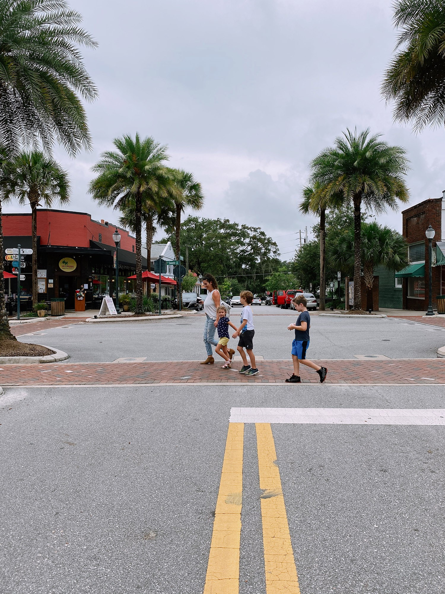 Spectacular Lake County, Florida Staycation Ideas for the Family! Downtown Mount Dora | Lake County by popular Florida blog, Fresh Mommy Blog: image of a mom and her kids walking a cross a street.