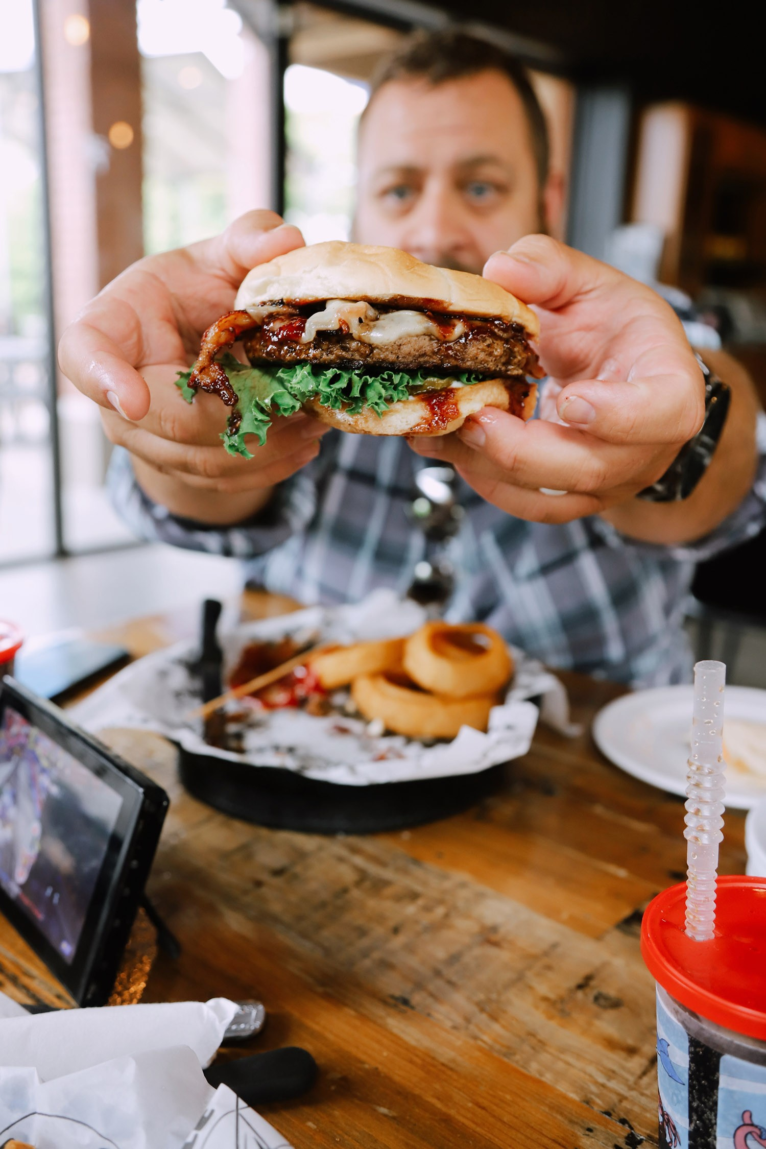 Spectacular Lake County, Florida Staycation Ideas for the Family! Bacon Brie Burger at Puddle Jumpers | Lake County by popular Florida blog, Fresh Mommy Blog: image of a man holding a brie burger at Puddle Jumpers.