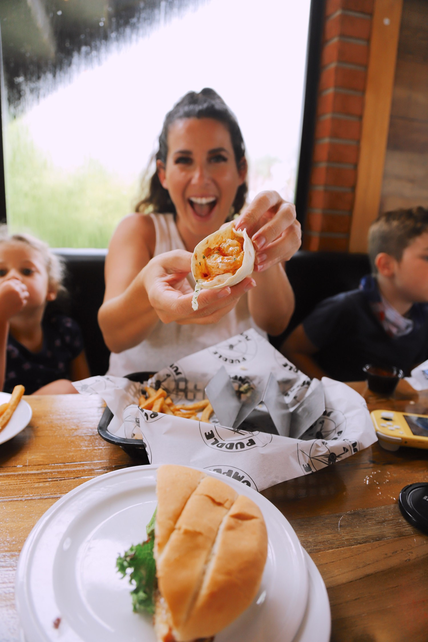 Spectacular Lake County, Florida Staycation Ideas for the Family! Spicy Shrimp Tacos at Puddle Jumpers | Lake County by popular Florida blog, Fresh Mommy Blog: image of a family eating food at Puddle Jumpers.