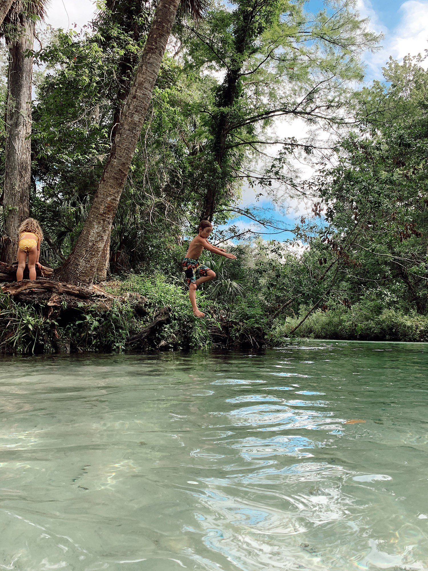Tips for an Amazing Weeki Wachee Kayaking Florida Staycation. Visit Florida Travel ideas from top lifestyle blogger Tabitha Blue of Fresh Mommy Blog. | Weeki Wachee Kayaking by popular Florida blog, Fresh Mommy Blog: image of a boy jumping into the water.