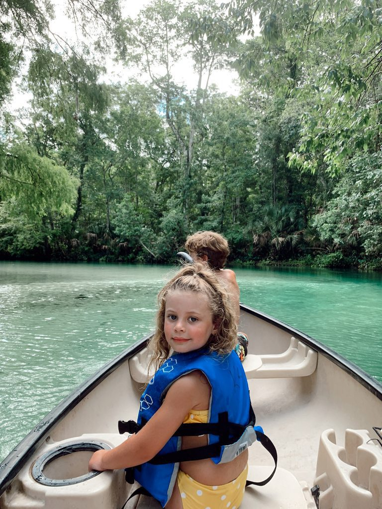 Tips for an Amazing Weeki Wachee Kayaking Florida Staycation. Visit Florida Travel ideas from top lifestyle blogger Tabitha Blue of Fresh Mommy Blog. | Weeki Wachee Kayaking by popular Florida blog, Fresh Mommy Blog: image of a little girl wearing a yellow and white polka dot bikini as she sits in a canoe.