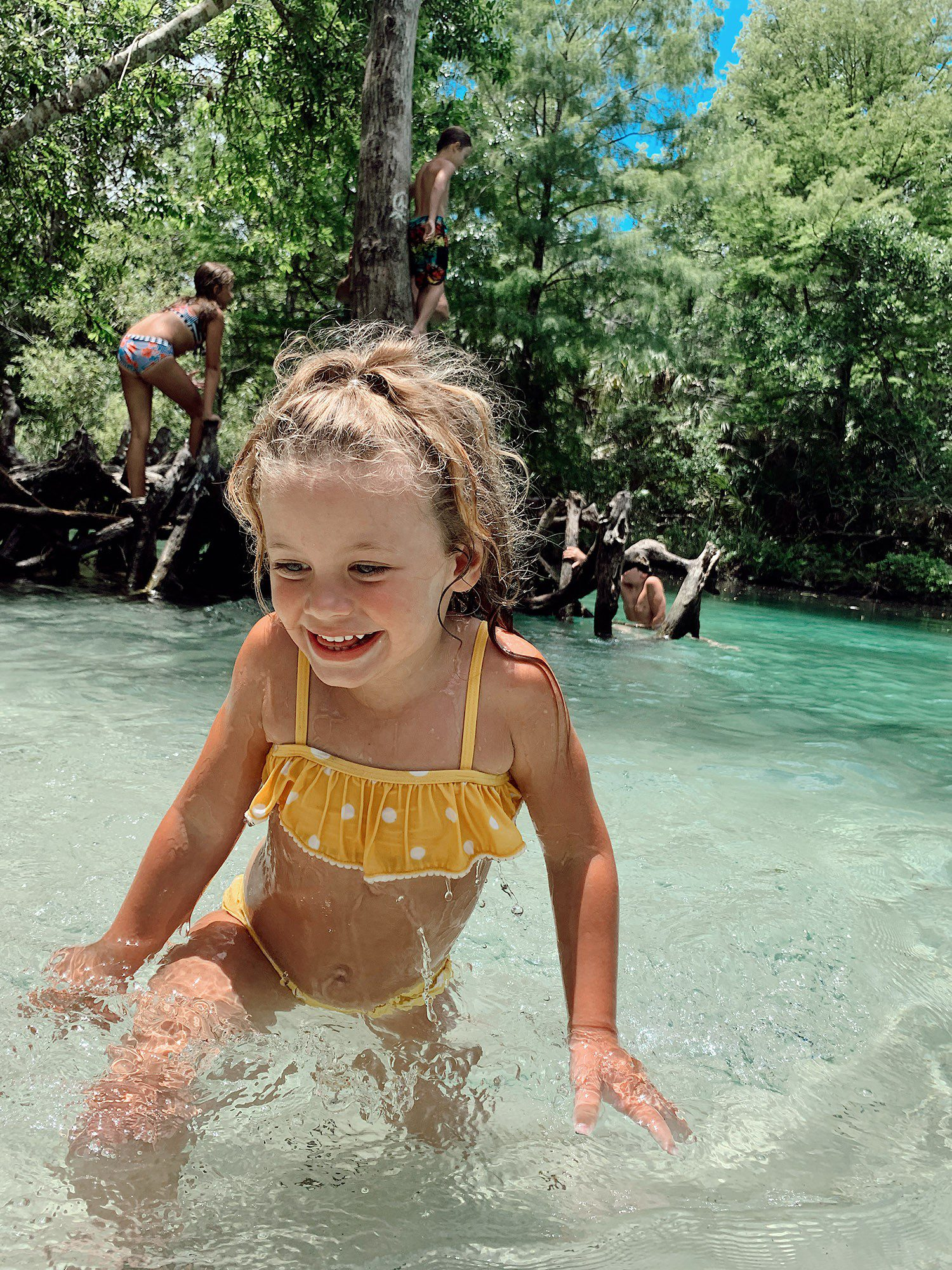 Tips for an Amazing Weeki Wachee Kayaking Florida Staycation. Visit Florida Travel ideas from top lifestyle blogger Tabitha Blue of Fresh Mommy Blog. | Weeki Wachee Kayaking by popular Florida blog, Fresh Mommy Blog: image of a little girl wearing a yellow and white polka dot bikini and playing in the water.