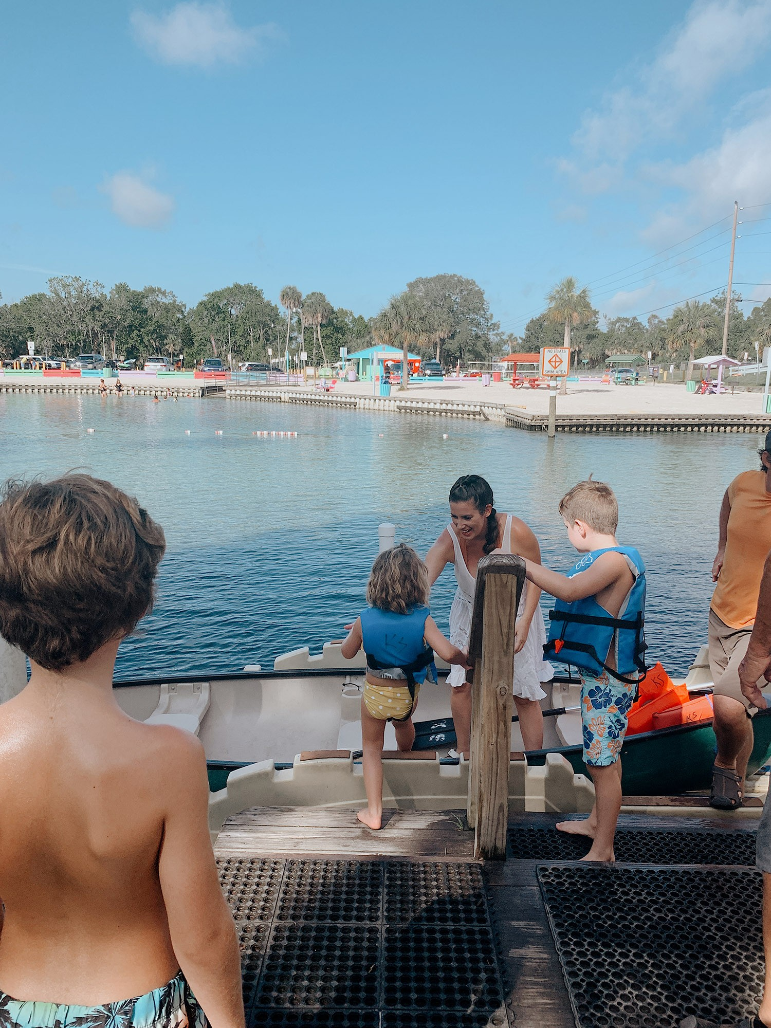 Tips for an Amazing Weeki Wachee Kayaking Florida Staycation. Visit Florida Travel ideas from top lifestyle blogger Tabitha Blue of Fresh Mommy Blog. | Weeki Wachee Kayaking by popular Florida blog, Fresh Mommy Blog: image of Tabitha Blue helping her kids climb into a canoe.