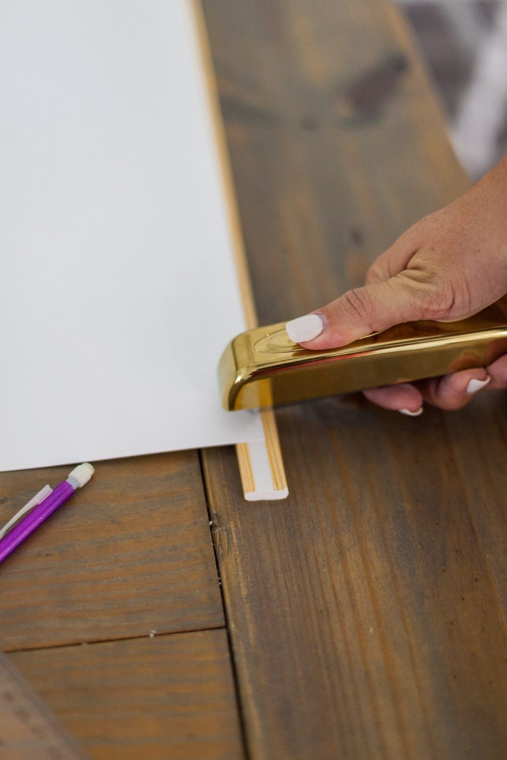 Click through for a fun, EASY DIY poster hanger tutorial. You can make your own DIY poster hanger for $3 in just a few short minutes! | DIY Poster Hanger by popular Florida DIY blog, Fresh Mommy Blog: image of a woman attaching a poster board to some wood moulding with a gold stapler.