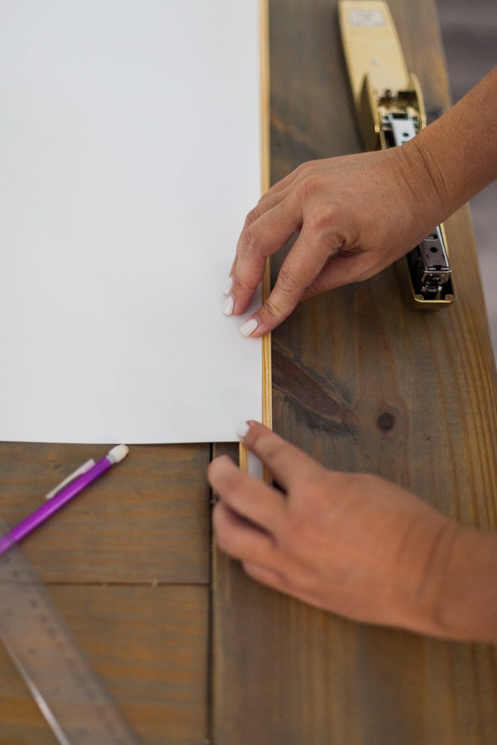 Click through for a fun, EASY DIY poster hanger tutorial. You can make your own DIY poster hanger for $3 in just a few short minutes!   DIY Poster Hanger by popular Florida DIY blog, Fresh Mommy Blog: image of a woman attaching a poster board to some wood moulding.
