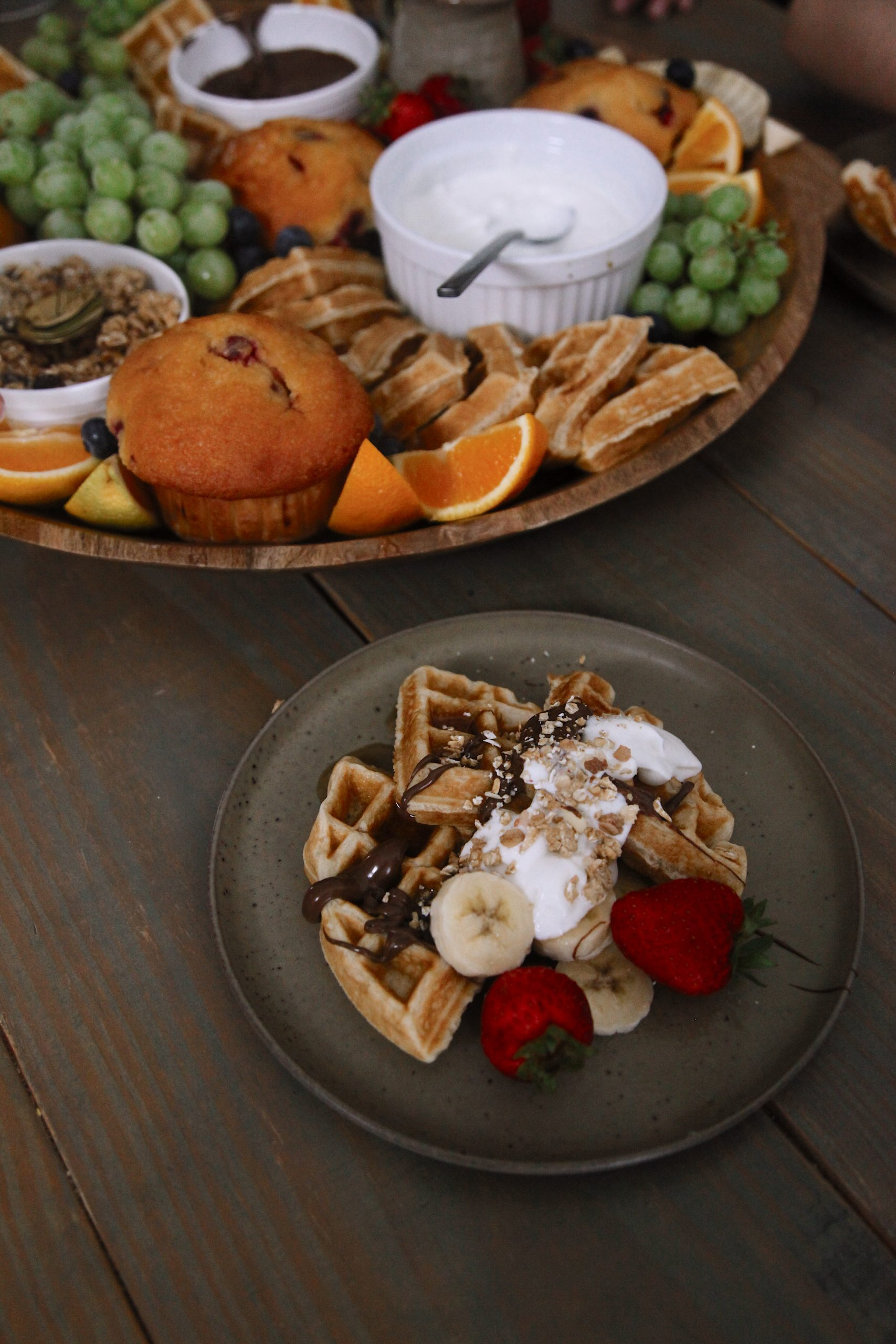 Easy Waffle Recipe for an Amazing Breakfast for Dinner Family Night - Chicken and Waffles Breakfast Board | xWaffle Recipe by popular Florida lifestyle blog, Fresh Mommy Blog: image of a wooden board filled with waffles, muffins, grapes, strawberries, orange slices, granola, fried chicken, yogurt, and chocolate sauce. | Waffle Recipe by popular Florida lifestyle blog, Fresh Mommy Blog: image of a plate of waffles topped with greek yogurt, chocolate sauce, granola, bananas, and strawberries.