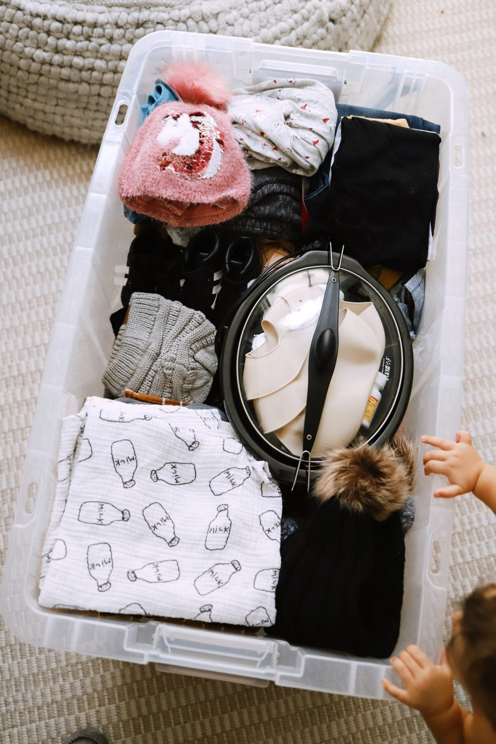 Road Trip Packing Tips by popular Florida travel blog, Fresh Mommy Blog: image of a clear storage container filled with kids clothing and baby essentials.