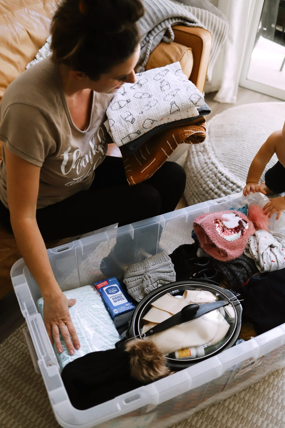 Road Trip Packing Tips by popular Florida travel blog, Fresh Mommy Blog: image of a mom packing a clear storage container with kids clothing and baby essentials.