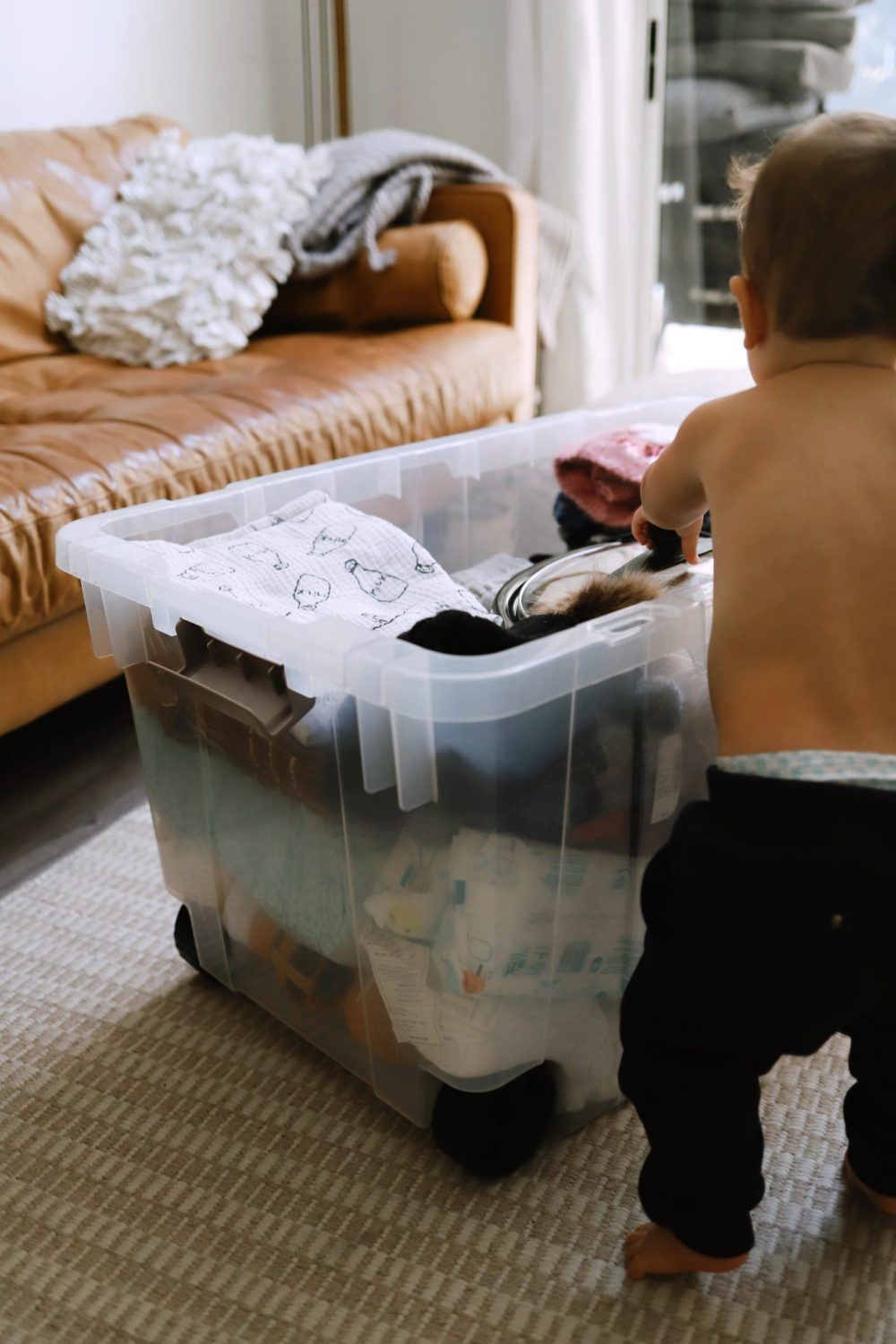 Road Trip Packing Tips by popular Florida travel blog, Fresh Mommy Blog: image of a baby getting in to a clear storage bin filled with clothing and baby essentials.