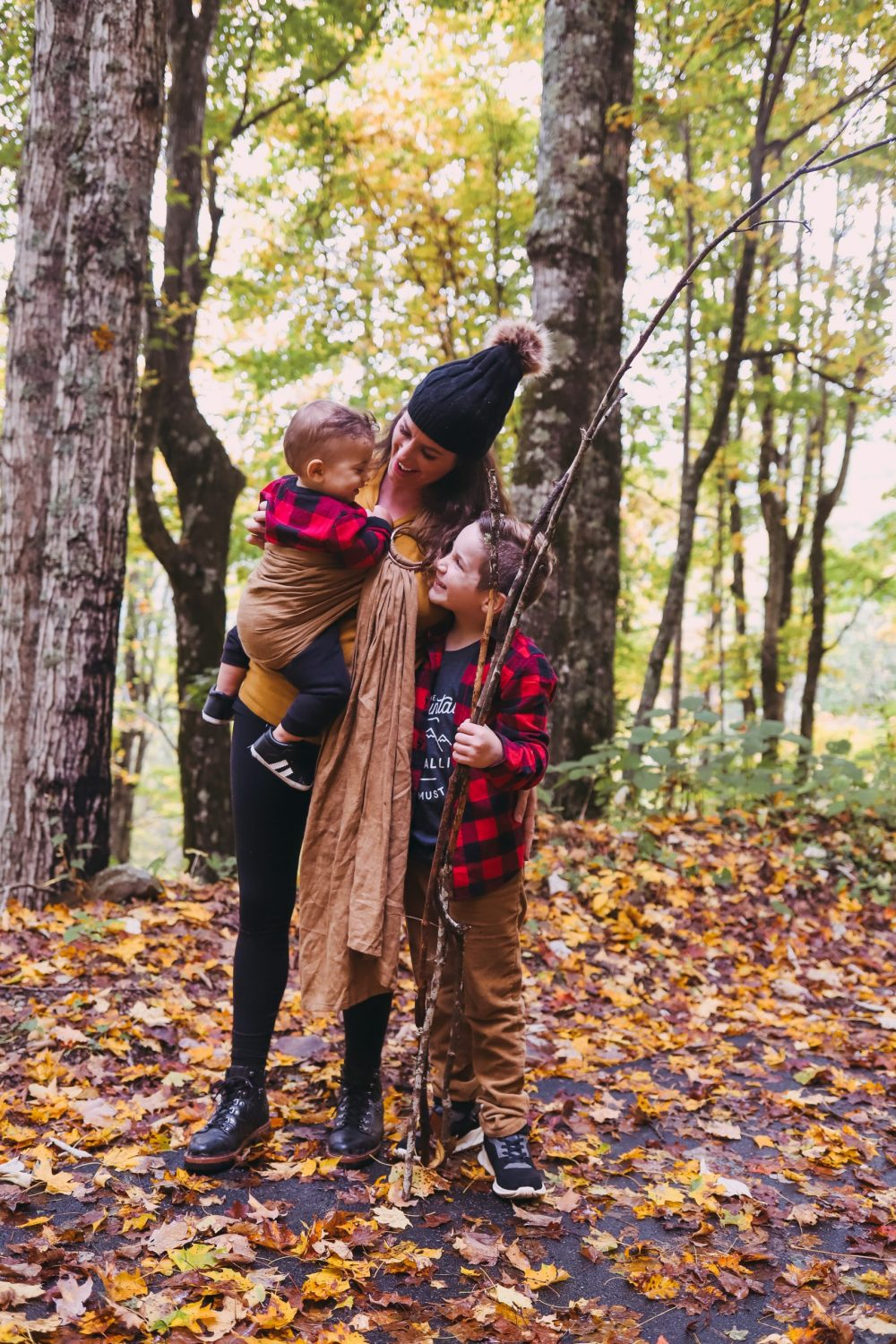Road Trip Packing Tips by popular Florida travel blog, Fresh Mommy Blog: image of a mom and two of her young sons standing on a path covered with fallen yellow leaves.