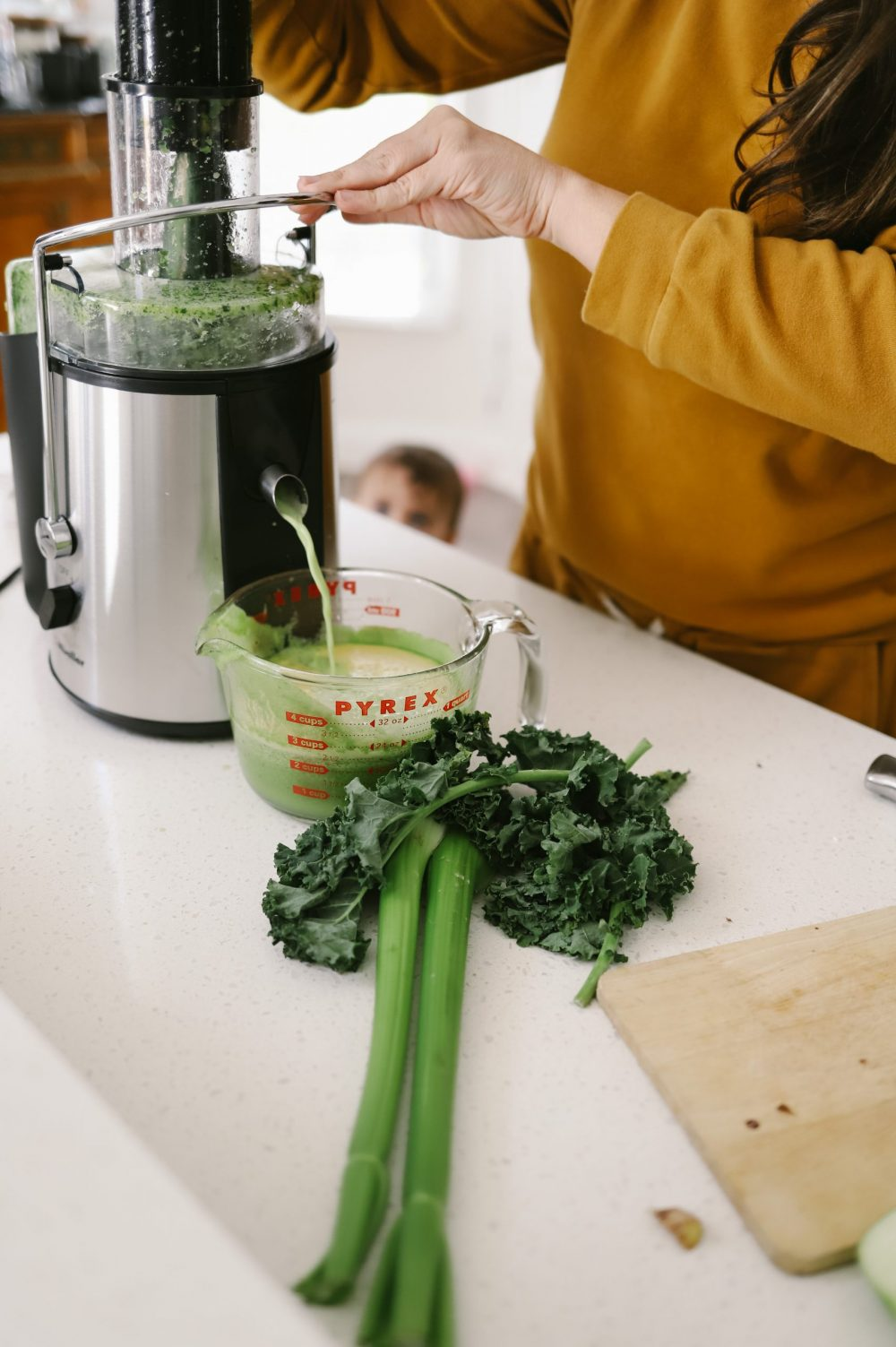 The Best Easy Clean Juicer Review for 2021: We tested easy clean juicers and this is what we found. |Easy Clean Juicer by popular Florida lifestyle blog, Fresh Mommy Blog: image of a woman making green juice in her easy clean juicer.