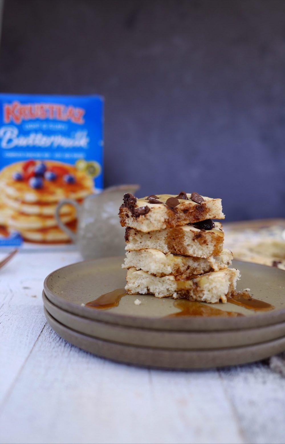 Amazingly Easy Sheet Pan Pancakes With Krusteaz Buttermilk Pancake Mix. Family breakfast ideas with 37 pancake add-in ideas. Big batch breakfast with baked pancakes to feed a crowd. |Krusteaz Buttermilk Pancake Mix by popular Florida lifestyle blog, Fresh Mommy: image of stacked sheet pan pancake slices.