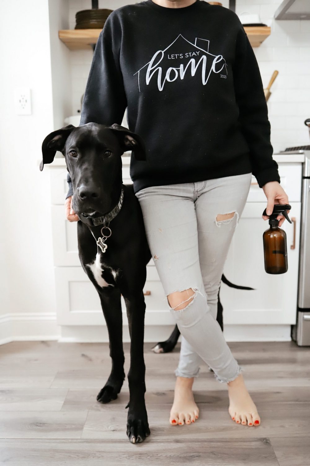 Essential Oils Safe for Dog Deodorizer Spray |Dog Deodorizer Spray by popular Florida lifestyle blog, Fresh Mommy Blog:image of a woman wearing a Let's Stay Home sweatshirt and standing next to her black Great Dane dog
