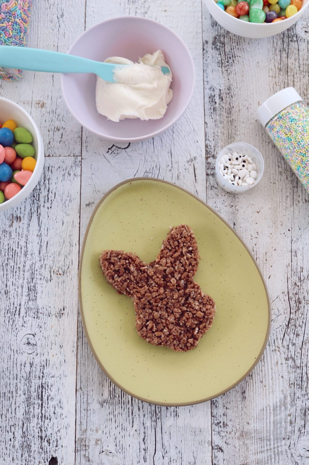 Simple Chocolate Easter Bunny Rice Krispies treats from top lifestyle blogger Tabitha Blue of Fresh Mommy Blog |Chocolate Rice Krispies Treats by popular Florida lifestyle blog, Fresh Mommy Blog: image of Easter Bunny shaped chocolate Rice Krispies treats, boxes of Cocoa Krispies in a Publix reusable shopping bag, a bowl of white frosting, pastel sprinkles, and white ceramic bowls filled with egg shaped jelly beans.