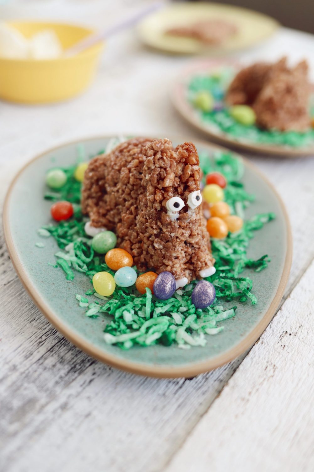 Simple Chocolate Easter Bunny Rice Krispies treats from top lifestyle blogger Tabitha Blue of Fresh Mommy Blog |Chocolate Rice Krispies Treats by popular Florida lifestyle blog, Fresh Mommy Blog: image of Easter Bunny shaped chocolate Rice Krispies treats,  a bowl of white frosting, pastel sprinkles, and white ceramic bowls filled with egg shaped jelly beans.