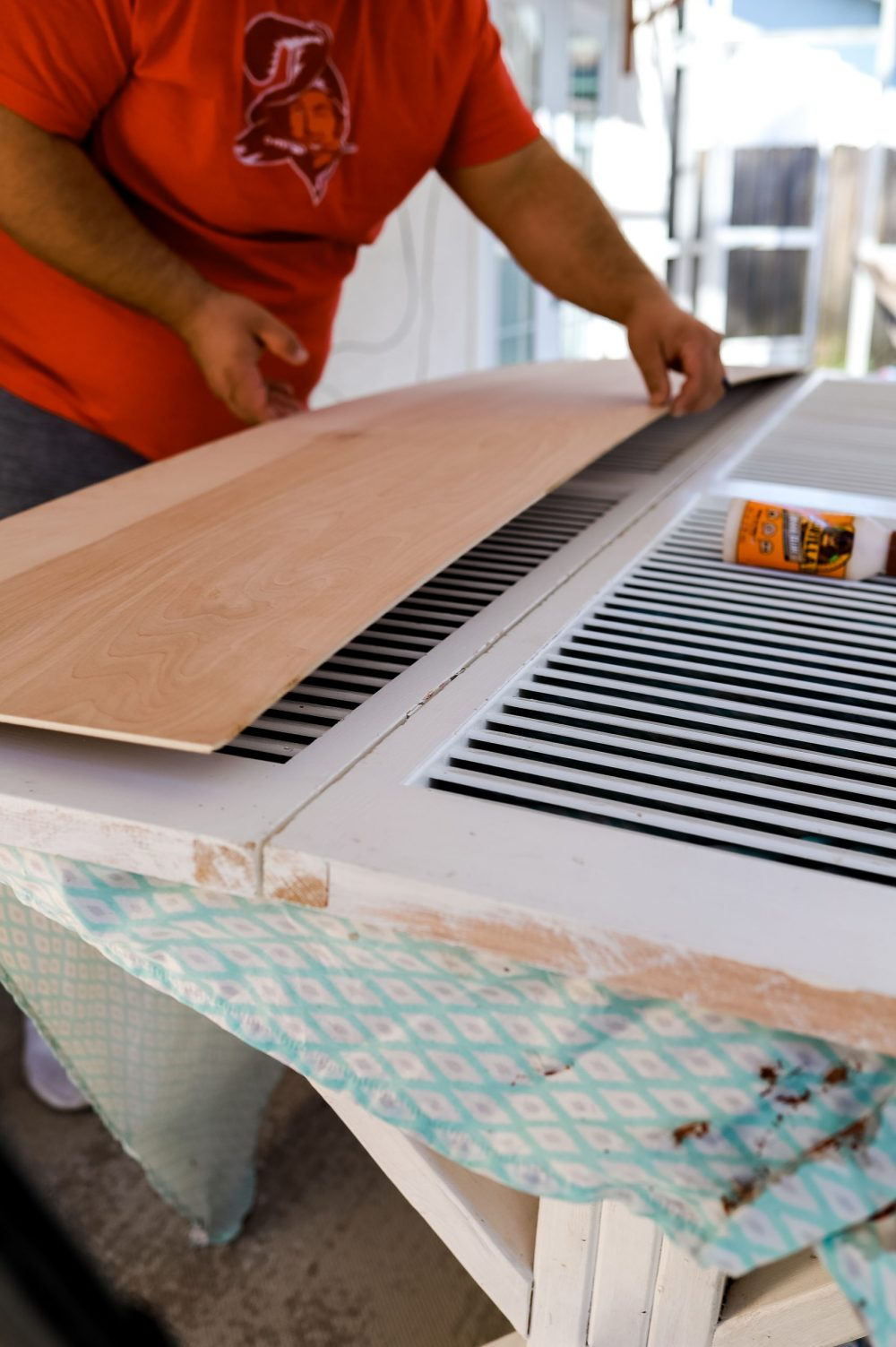 Home Refresh Ideas: DIY Closet Door Upgrade Tutorial. How to update Bi-fold closet doors on a budget. Easy how-to for updating old bifold closet doors and save money (save the hundreds it would cost to replace them!). |DIY Closet Door by popular Florida lifestyle blog, Fresh Mommy Blog: before image of a man gluing a wooden board to the front of a bifold closet door.