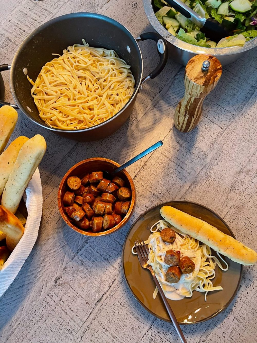 Omaha Steaks Meals featured by top FL lifestyle blogger, Tabitha Blue of Fresh Mommy Blog. - Italian Sausage Alfredo | Omaha Steaks Meals by popular Florida lifestyle blog, Fresh Mommy Blog: image of cut up sausage next to fettuccine noodles and a bowl of salad.