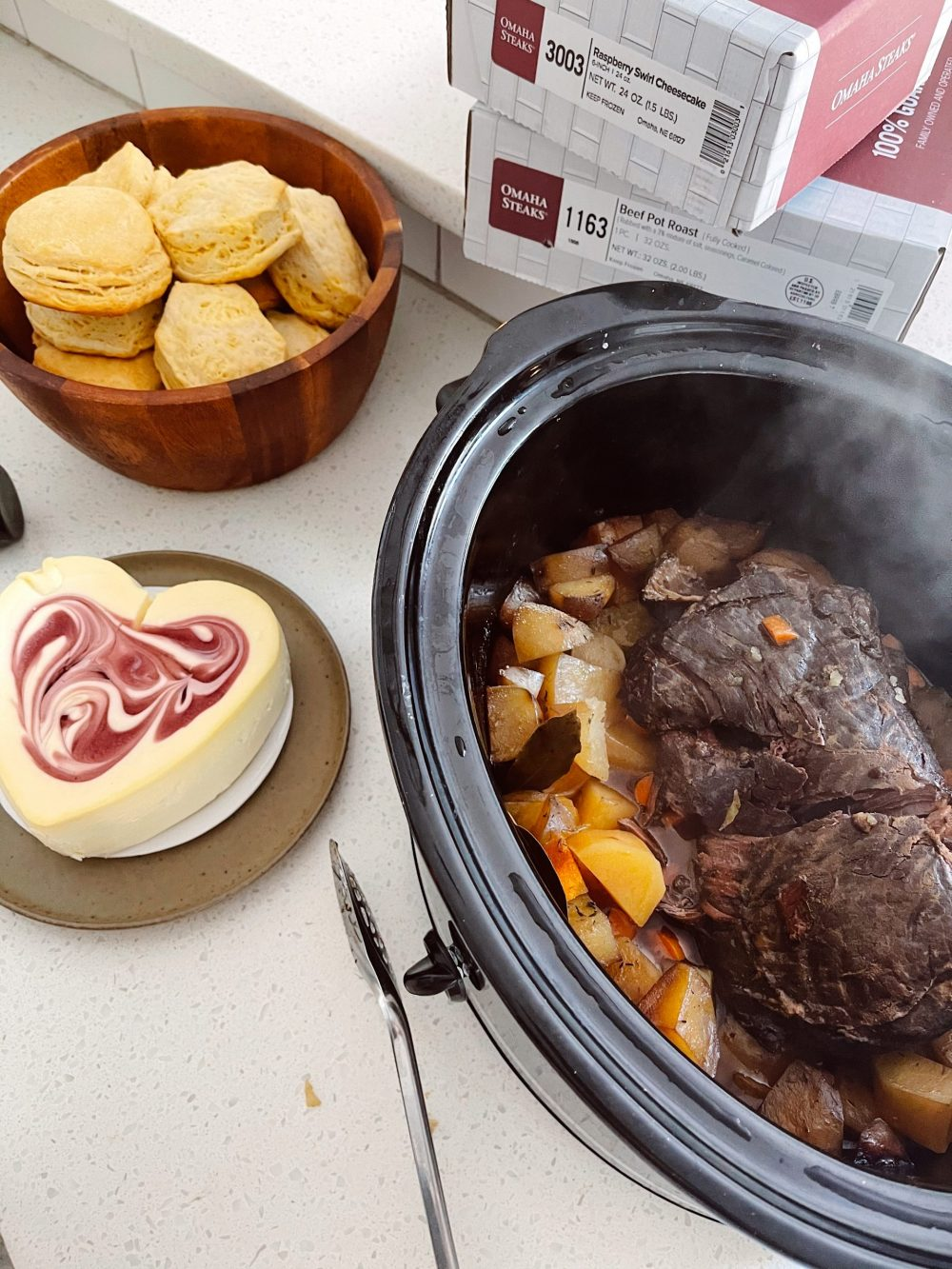 Omaha Steaks Meals featured by top FL lifestyle blogger, Tabitha Blue of Fresh Mommy Blog. - Pot Roast | Omaha Steaks Meals by popular Florida lifestyle blog, Fresh Mommy Blog: image of slow cooker pot roast next to a wooden bowl filled with biscuits and a heart shaped cheese cake.