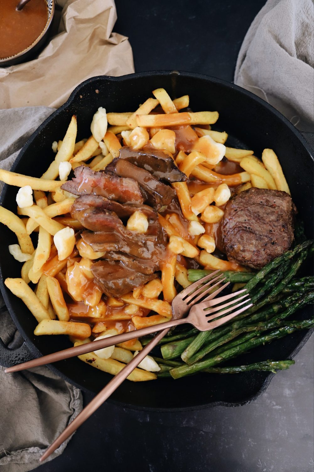 An Easy Steak Poutine Recipe with Fries and Gravy |Poutine Recipe by popular Florida lifestyle blog, Fresh Mommy Blog: image of steak poutine and asparagus in a black skillet.