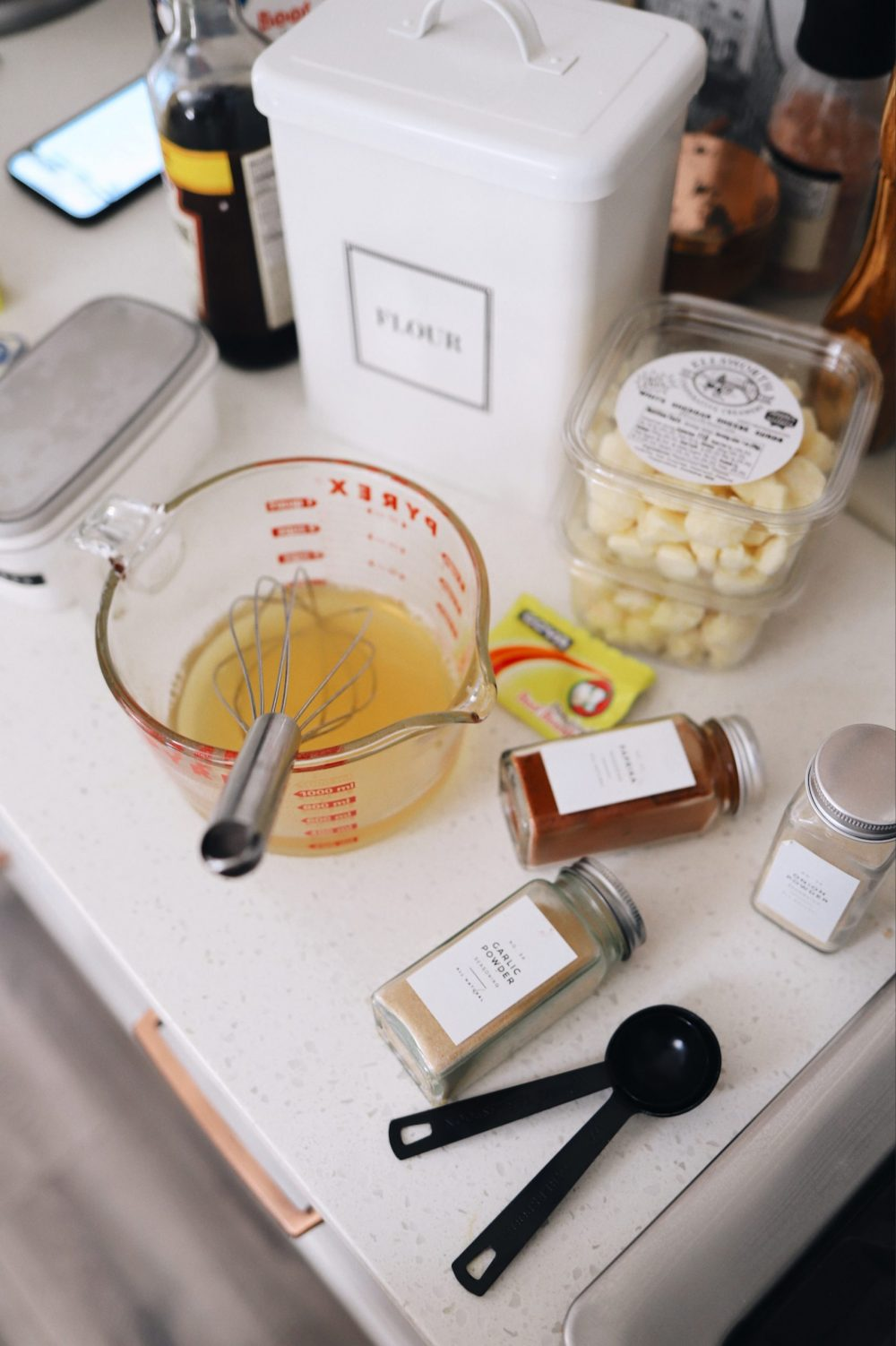 An Easy Steak Poutine Recipe with Fries and Gravy |Poutine Recipe by popular Florida lifestyle blog, Fresh Mommy Blog: image of spice jars, chicken stock in a pyrex glass measuring cup, and cheese curds.