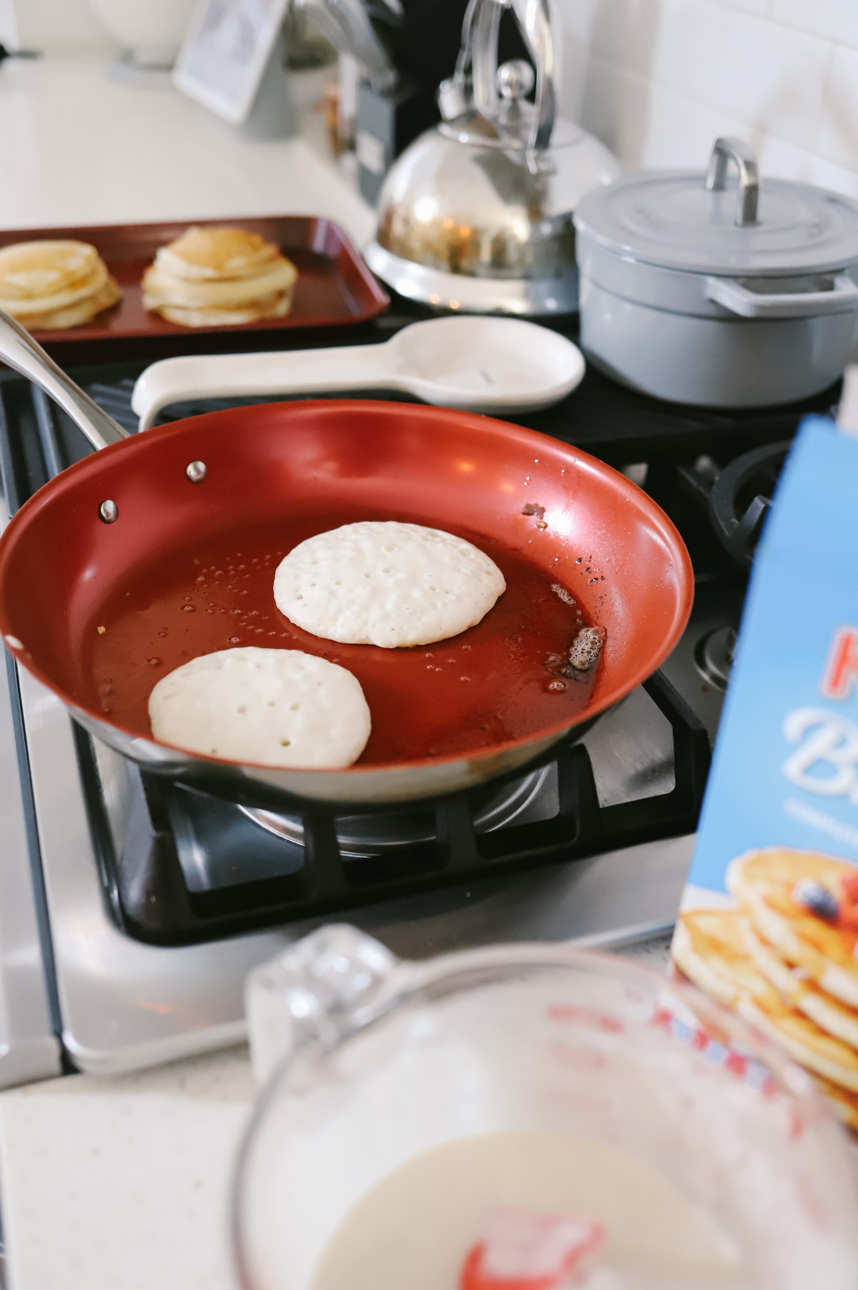 How to cook pancakes + The best Spring Breakfast Board |Pancake Board by popular Florida lifestyle blog, Fresh Mommy Blog: image of pancakes cooking on a gas range stove next to a box of Krusteaz pancake mix and a Pyrex measuring cup filled with pancake batter.